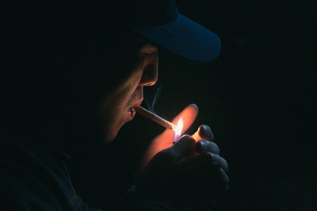אדם מעשן סיגריה בחושך