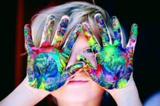 ילד עם ידיים מכוסות צבעים מסתיר את עיניו